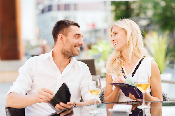 happy couple with wallet paying bill at restaurant