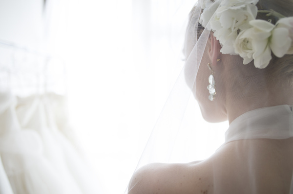 The bride wears a white flower in her hair